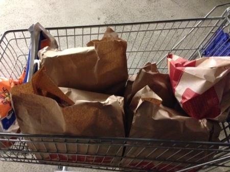 Die Waren kommen in brauen Tüten in den Einkaufswagen zurück.