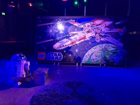 Das Mosaik des X-Wing-Fighters am Hallenausgang. Davor R2D2, auch aus Lego.