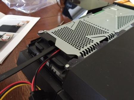 Die Abdeckung der Game Bar-Verkleidung aufsetzen und die Festplattenanschlusskabel durch die Öffnung ziehen.