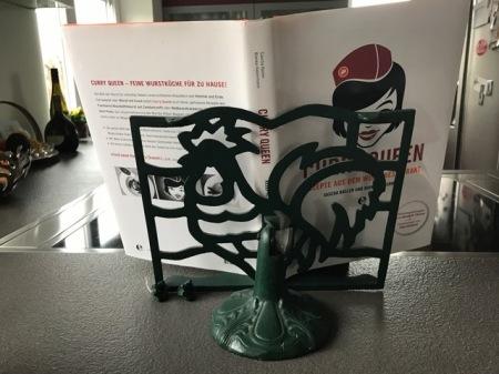 Der Hahn hält das Kochbuch.