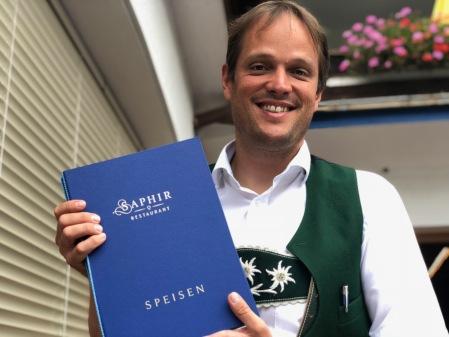 Hotelier Armin Gross mit der Speisekarte des Saphir.